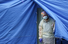 FILE - In this Nov. 11, 2020, file photo, medical works operate a testing tent at a COVID-19 mobile testing site  in the…
