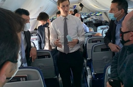 Senior White House adviser Jared Kushner, center, briefly removes his mask to speak to reporters as he leads a delegation…
