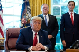 President Donald Trump listens while on a phone call with leaders of Sudan and Israel in the Oval Office of the White House,…