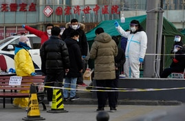 Residents line up for coronavirus tests at tents set up on the streets of Beijing on Sunday, Dec. 27, 2020. Beijing has urged…