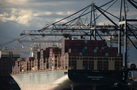 Gantry cranes work over the Seaspan Harrier container ship at Global Container Terminals in Elizabeth, N.J., Monday, May 11,…