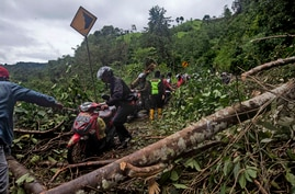 Motorists make their way through a road affected by an earthquake-triggered landslide near Mamuju, West Sulawesi, Indonesia,…