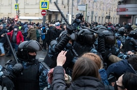 Police officers clash with people during a protest against the jailing of opposition leader Alexei Navalny in Moscow, Russia,…