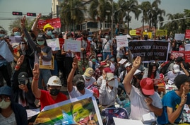 Demonstrators display placards during a protest close to Indonesian Embassy in Yangon, Myanmar, Tuesday, Feb. 23, 2021. Anti…