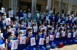 """Teachers from the Yangon Education University flash the three-finger protest gesture while holding signs that read: """"Civil…"""