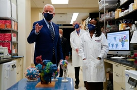 President Joe Biden speaks as Kizzmekia Corbett, an immunologist with the Vaccine Research Center at the National Institutes of…