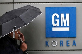 FILE - In this April 23, 2018, file photo, a worker of General Motors Korea talks on the mobile phone outside the factory in…