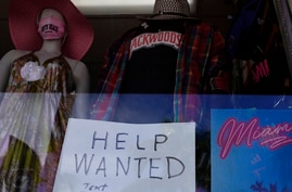 """A """"Help Wanted,"""" sign is shown in the window of a souvenir shop, Thursday, Jan. 7, 2021, in Miami Beach, Fla.  Layoffs spiked…"""