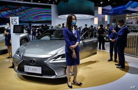 Staff members wearing face masks to help curb the spread of the coronavirus gather near the Lexus car models on display at the…
