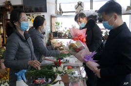 Men look at floral bouquets at a flower shop next to the Pyongyang Railway Station on International Women's Day in Pyongyang,…