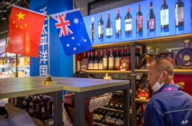 A visitor wearing a face mask to protect against the coronavirus looks at a display of Australian wines at the China…