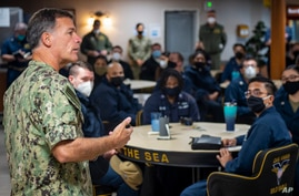 In this Feb. 8, 2021, photo provided by the U.S. Navy, Adm. John Aquilino, commander, U.S. Pacific Fleet, speaks with sailors…