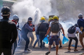 Anti-coup protesters use fire extinguishers to reduce the impact of teargas fired by riot policemen in Yangon, Myanmar Tuesday,…