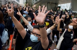 """Supporters gesture with five fingers, signifying the """"Five demands - not one less"""" outside a court in Hong Kong Monday, March 1…"""