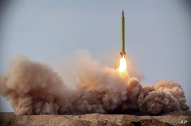 FILE - In this file photo released Jan. 16, 2021, by the Iranian Revolutionary Guard, a missile is launched in a drill in Iran…