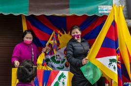 Exile Tibetans sell flags at a gathering to mark the anniversary of the Tibetan Uprising Day in Dharmsala, India, Wednesday,…