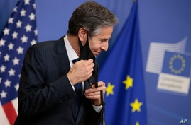 U.S. Secretary of State Antony Blinken takes off his protective face mask prior to addressing a media conference at EU…