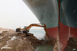 This photo released by the Suez Canal Authority on Thursday, March 25, 2021, shows a backhoe trying to dig out the keel of the…