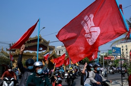 Engineers carry flags bearing the three-fingers salute as they drive their motorcycles during an anti-coup protest in Mandalay,…