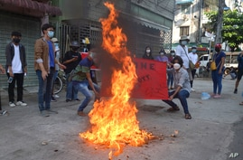 Anti-coup protesters burn a Chinese flag during a demonstration in Yangon, Myanmar on Wednesday, April 7, 2021. Protesters…
