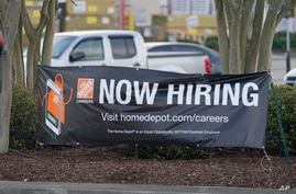 A roadside banner beckons potential employees outside a Home Depot store in Hattiesburg, Miss., March 27, 2021. The number of…
