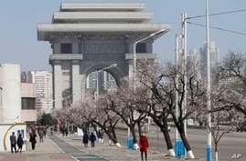 People walk in the street near the Arch of Triumph in Pyongyang, on Monday, April 5, 2021. (AP Photo/Cha Song Ho)