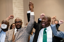Philonise Floyd, brother of George Floyd, left, and attorney Ben Crump raise their hands in triumph during a news conference…