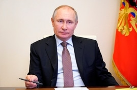 Russian President Vladimir Putin listens during a meeting on labor issues via video conference at the Novo-Ogaryovo residence…