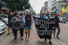 Anti-coup protesters shout slogan with a banner reading ''Carry on revolution! We do not accept as the military slave,'' in…