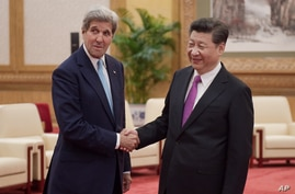 Chinese President Xi Jinping shakes hands with U.S. Secretary of State John Kerry prior to a meeting at the Great Hall of the…