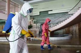 Restaurant staff, in protective suit, disinfect the floor of Chongchun Restaurant in Pyongyang, on Thursday, May 13, 2021. (AP…