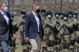 Polish President Andrzej Duda, right, reviews the honor guard with Romanian President Klaus Iohannis before the Justice Sword…