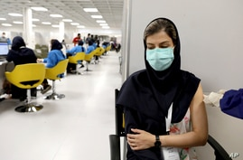 A medical worker receives the Sinopharm vaccine for COVID-19 at the Iran Mall shopping center in Tehran, Iran, Monday, May 17,…