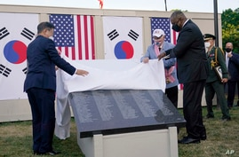 South Korean President Moon Jae-in, left, and Secretary of Defense Lloyd Austin, right, look at a replica of a section of the…