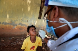A health worker takes the nasal swab sample of a boy to test for COVID-19 in Gauhati, India, Friday, May 14, 2021. (AP Photo…