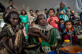 Displaced Tigrayan women Tarik, 60, center, and Meresaeta, left, who fled from the town of Samre, roast coffee beans over a…