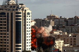 Smoke and flames rise moments after an Israeli airstrike struck an 11-story building housing The Associated Press and other…