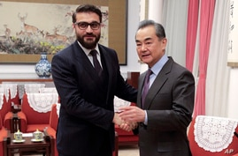 Afghanistan National Security Advisor Hamdullah Mohib, left, shakes hands with Chinese Foreign Minister Wang Yi before…