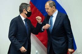 U.S. Secretary of State Antony Blinken, left, greets Russian Foreign Minister Sergey Lavrov, right, as they arrive for a…