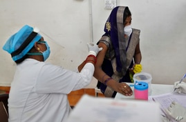A woman receives the AstraZeneca vaccine for COVID-19 at a hospital in Prayagraj, India. Saturday, May 1, 2021. In hopes of…