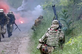 In this photo provided by the Russian Defense Ministry, Russian and Serbian soldiers in action during exercises near…