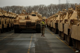 A U.S. soldier walks past parked armoured vehicles and tanks of the 1st Armored Brigade Combat Team and 1st Calvary Division,…