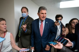 Sen. Joe Manchin, D-W.Va., is surrounded by reporters as senators rush to the chamber for votes ahead of the approaching…