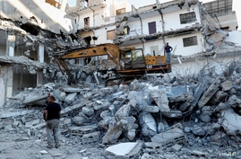 Workers remove the rubble of a building destroyed by an Israeli airstrike, in Gaza City, Tuesday, June 15, 2021. The building…