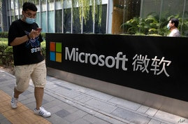A man looks at his smartphone as he walks by the Microsoft office in Beijing, China on Friday, Aug. 7, 2020. The Biden…