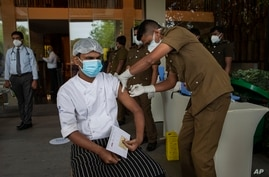 A Sri Lankan health worker administers Sinopharm COVID-19 vaccine to a staff member of a hotel in Weerawila, about 200…