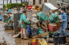 People clean their homes from mud and debris in Bad Neuenahr-Ahrweiler, Germany, Saturday, July 17, 2021. Due to strong rain…