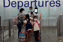 A girl waves farewell to friends as she departs for a permanent move to U.K. at the Hong Kong airport Wednesday, June 30, 2021…