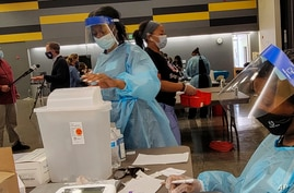 Licensed Vocational Nurses prepare Pfizer vaccines at a school-based vaccination clinic where students 12 and older will…