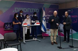 Israeli Prime Minister Naftali Bennett, front left, speaks to journalists with President Isaac Herzog, who received a third…